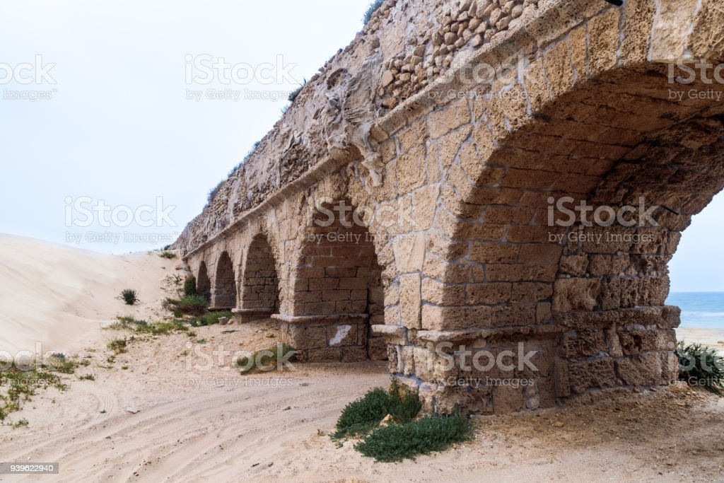 Remains  of the ancient Roman aqueduct on the Mediterranean coast near the Caesarea city in Israel stock photo