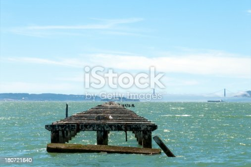 Remains of the Berkeley Pier, which once extended 3.5 miles into San Francisco Bay. The Golden Gate Bridge and Alcatraz are visible in the background, and a blimp is in the sky.