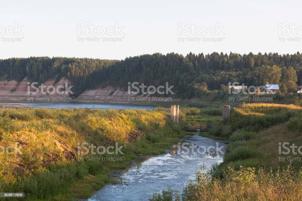 Remains of the Opokskogo hydroelectric complex in the rays of the setting sun. Village Threshold in Velikoustyugsky district, Vologda region stock photo