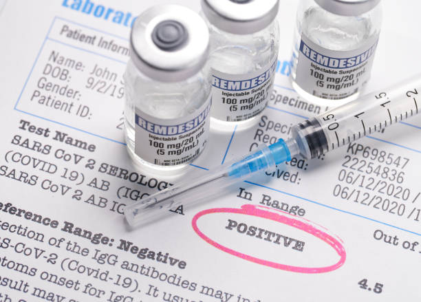 Remdesivir vials and syringe on covid-19 test results positive stock photo