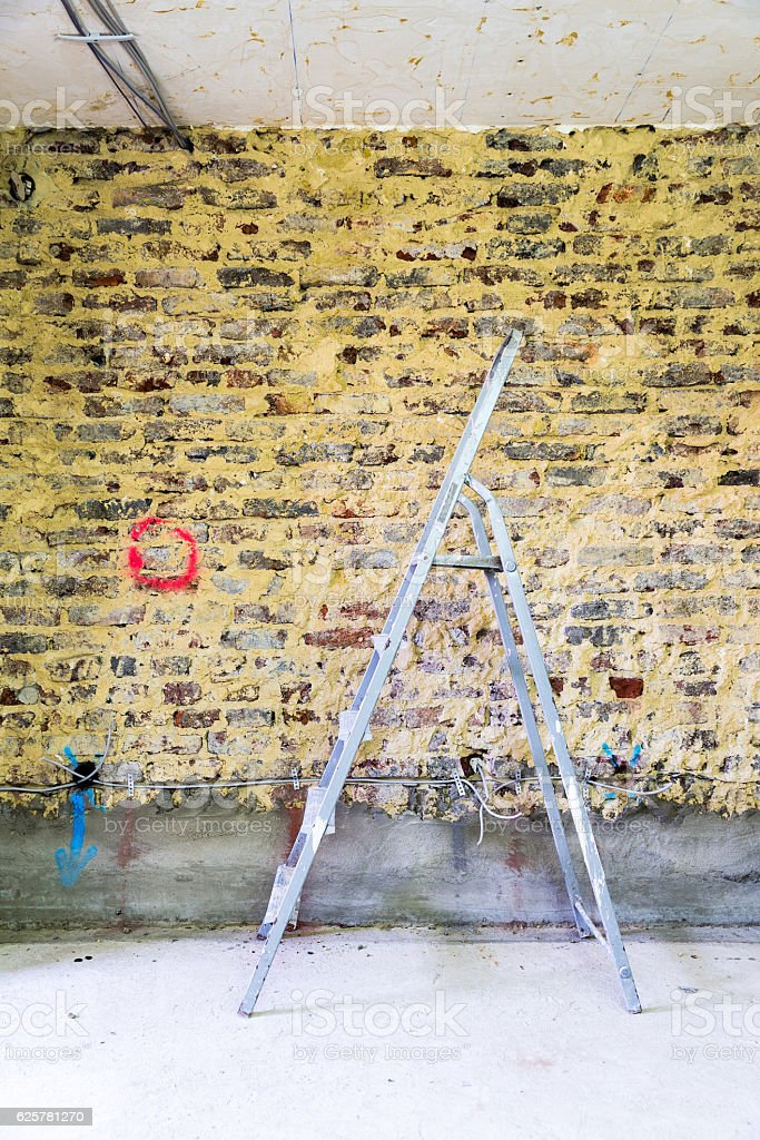 Remediation of brick wall and ladder stock photo