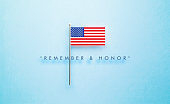 Remember and Honor Memorial Day message next to tiny American flag on blue  background. Horizontal composition with copy space. Front view.