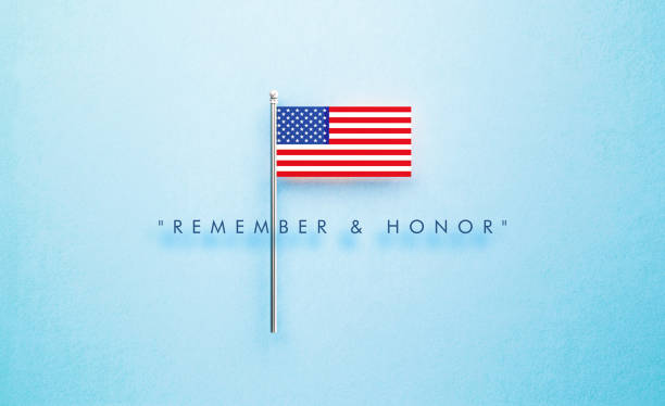 remember and honor memorial day message next to tiny american flag on blue background - memorial day стоковые фото и изображения