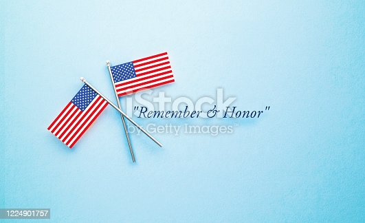 Remember and Honor Memorial Day message next to tiny American flag pair sitting on blue  background. Horizontal composition with copy space. Front view.