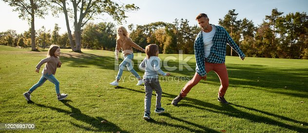 Full-length portrait of happy mother, father, little boy and girl running and playing catch game in autumn park. Family, parenthood, leisure and people concept. Horizontal shot.