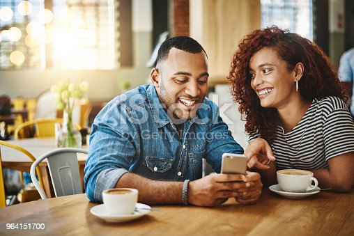 Cropped shot of an affectionate young couple looking at a cellphone while sitting in a coffee shop