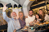 Family eating sushi and other Asian food in a Chinese restaurant and taking a selfie with a mobile phone. Three generation family, senior man, senior woman, mid adult man, mid adult woman and a girl, all Caucasian.