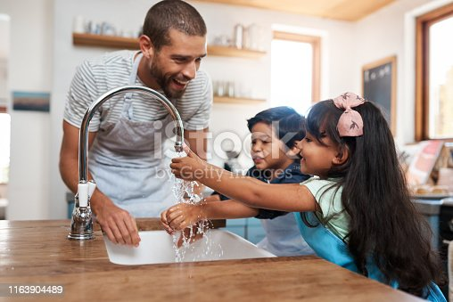 Cropped shot of a man and his two children washing their hands in the kitchen basin