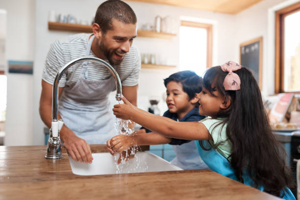 Remember to get in between your fingers Cropped shot of a man and his two children washing their hands in the kitchen basin between stock pictures, royalty-free photos & images