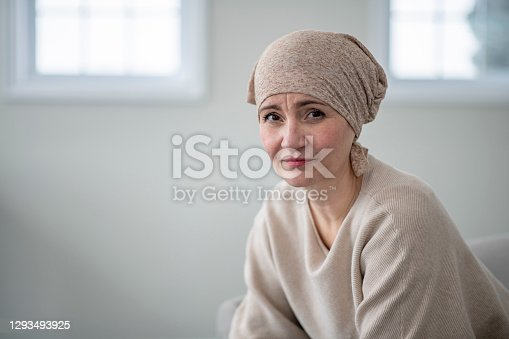 A beautiful and strong female cancer patient looks at the camera with a neutral expression. She wears a headscarf to cover her hair loss from chemotherapy.