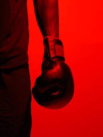 Red filtered shot of a sportsman  wearing boxing gloves