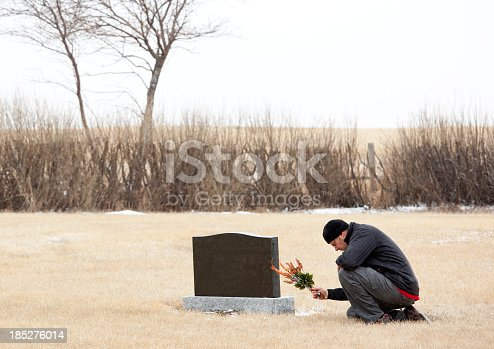 A man pays his respects at a grave. A man dressed in black for a funeral is bowing or praying at a gravestone. Themes include dying, death, grief, loss, grieving, sadness, tears, remembering, veterans day, memorial day, and lest we forget. Horizontal colour image taken in mid winter. Man is in his 30s, side view, Caucasian.