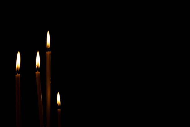 día de la conmemoración luto memorial funeral paz crematorio condolencia concepto. cierre horizontal paisaje quema cuatro encendió velas aisladas con llama amarillo naranja sobre fondo negro. - duelo fotografías e imágenes de stock