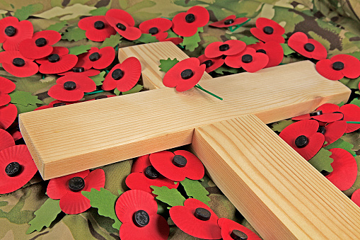 Remembrance day poppies surrounding a wooden cross