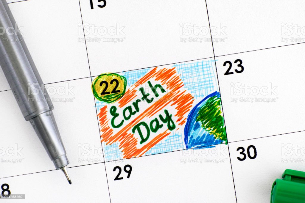 Reminder Earth Day in calendar with green pen. stock photo