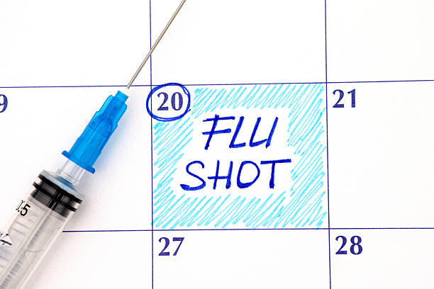 Reminder Flu Shot in calendar with syringe Reminder Flu Shot in calendar with syringe. Close up. flu shot stock pictures, royalty-free photos & images