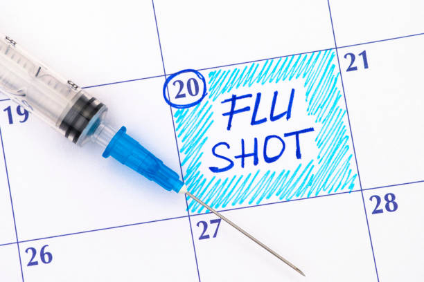 Reminder Flu Shot in calendar with syringe. Reminder Flu Shot in calendar with syringe. Close-up. flu vaccine stock pictures, royalty-free photos & images