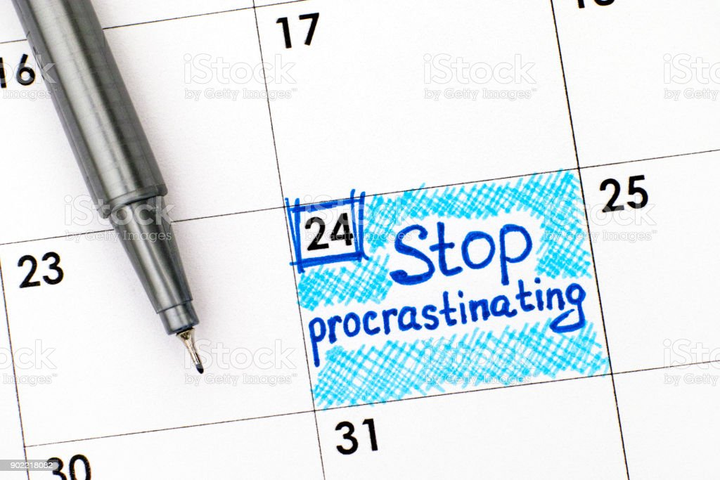 Reminder Stop Procrastinating in calendar with pen. Close-up. stock photo