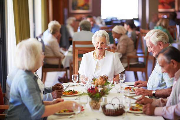 Reminiscing with friends at the dining table A group of elderly people having lunch together at a nursing home retirement community stock pictures, royalty-free photos & images