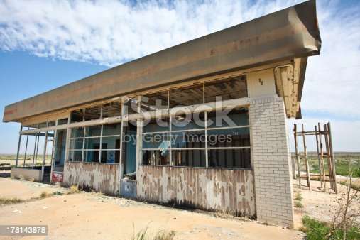 Wide view of abandoned service station with desert & blue sky in the background along Route 66 in New Mexico