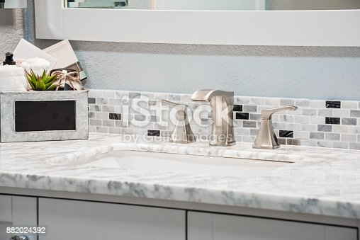 The newly installed sink, counter, and faucet in this residential bathroom.