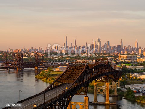 Aerial view on General Pulaski Bridge - Pulaski Skyway in front of remote Manhattan at sunset.