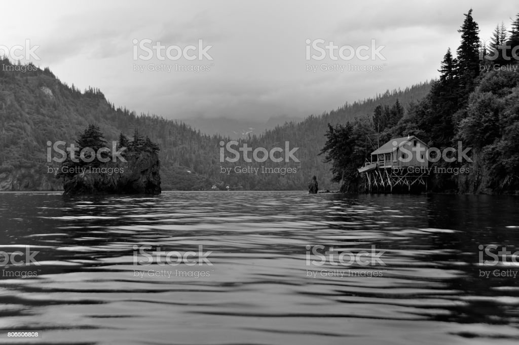 Remote Alaska cabin in the rain viewed from water, black and white stock photo