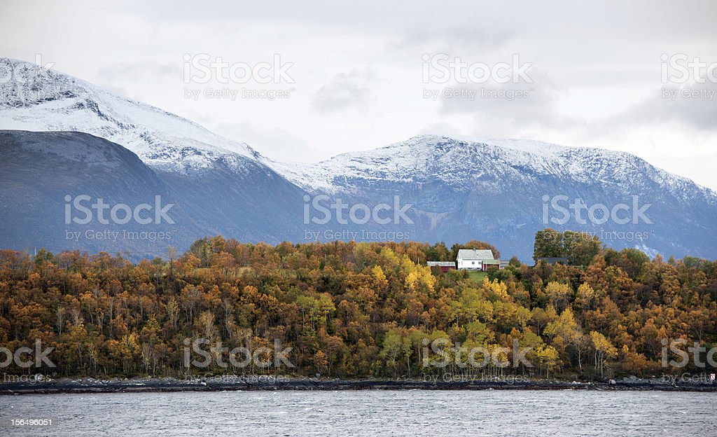 Remote coastal Norwegian white house in forest with mountains behind royalty-free stock photo