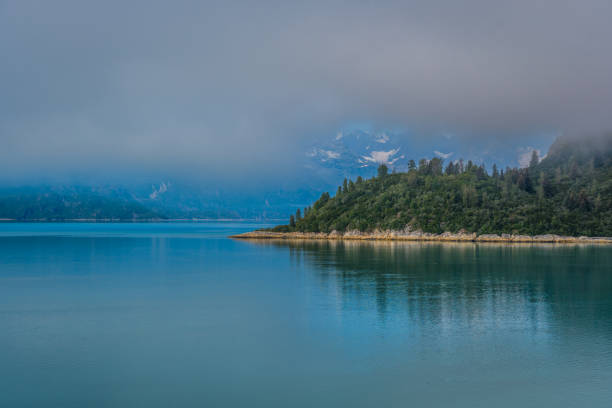 Remote coastline on a misty morning in the Alaska inside passage with snow capped mountains in the background stock photo