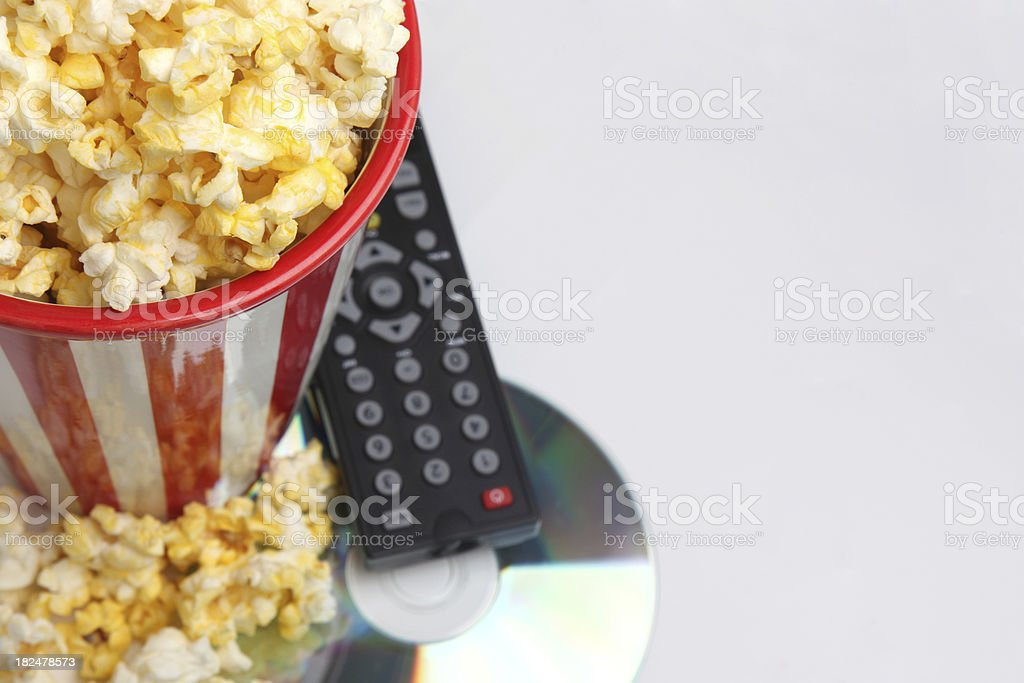 DVD, remote control, and popcorn sitting on gray background. stock photo