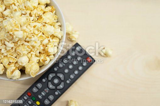 TV remote control and popcorn. Watch movies online in the bedroom.