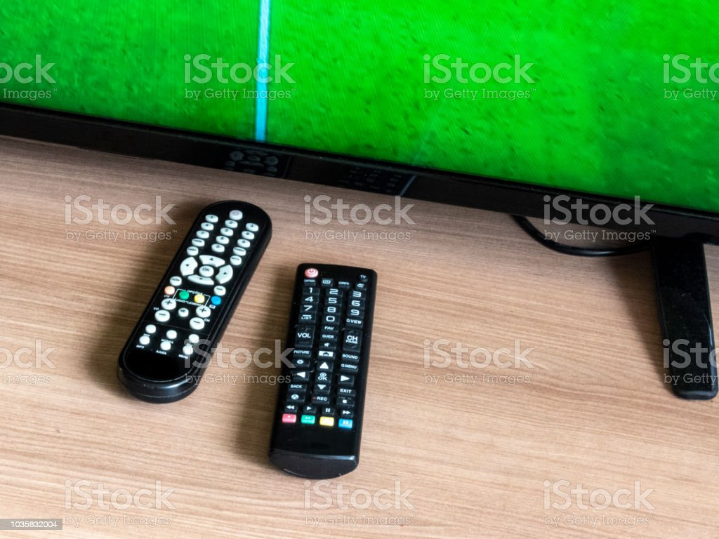 remote control and television with a soccer field on the screen