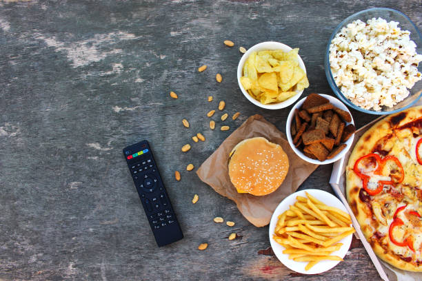 tv remote control, fast food on old wooden background. concept of junk eating. top view. flat lay. - telecomando background foto e immagini stock