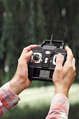 Remote control for unmanned drone, close-up. Transmitter for controlling moving device in male hands, blurred nature background. Electronics, hobby, aeromodelling concept