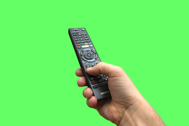 Remote control in hand on isolated green screen background, path included Remote control in hand on chroma key background. Working Path included. remote control stock pictures, royalty-free photos & images