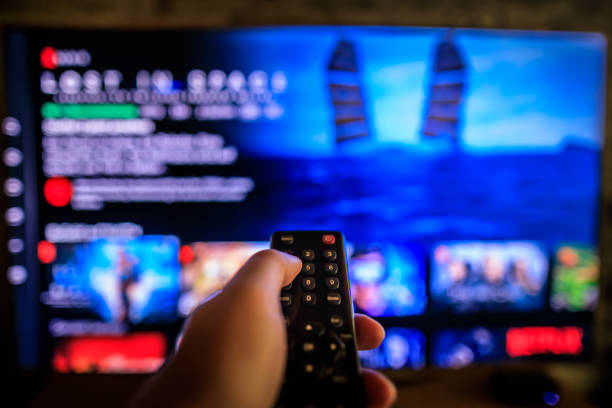 TV remote control in the foreground, Video on demand screen in the blurry background TV remote control in the foreground, Video on demand screen in the blurry background, streaming downloading stock pictures, royalty-free photos & images