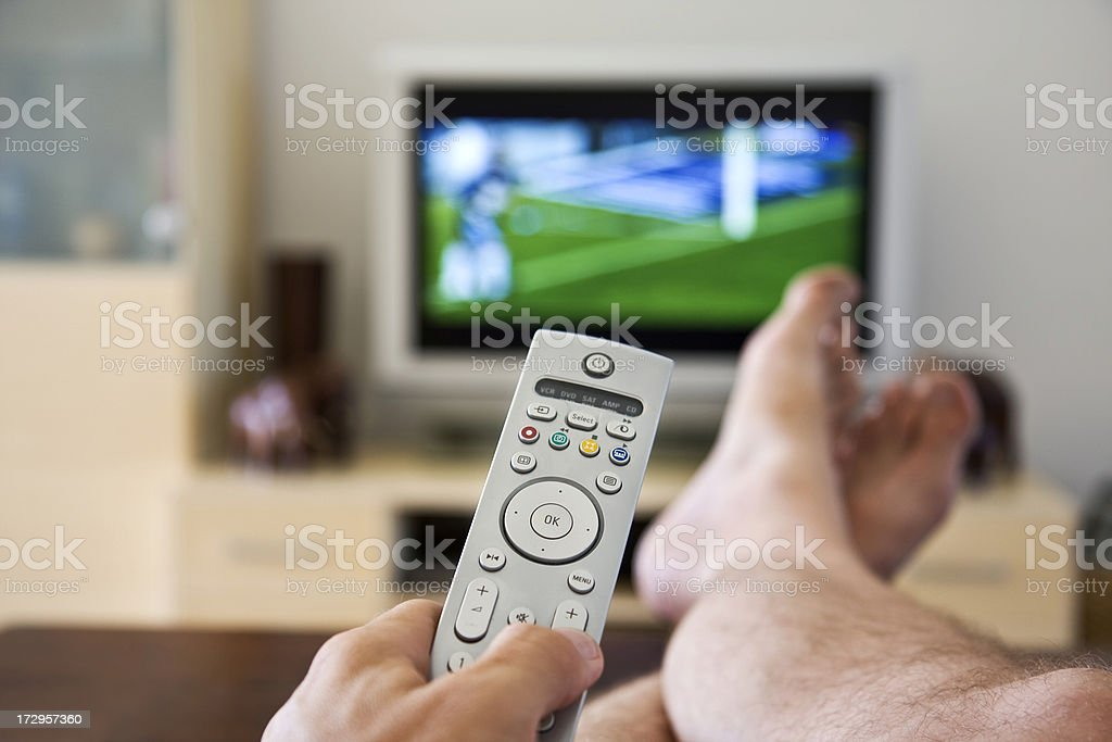 Remote Control. Lazy husband watching sport. stock photo