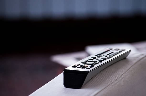 TV Remote Control on Arm of Chair stock photo