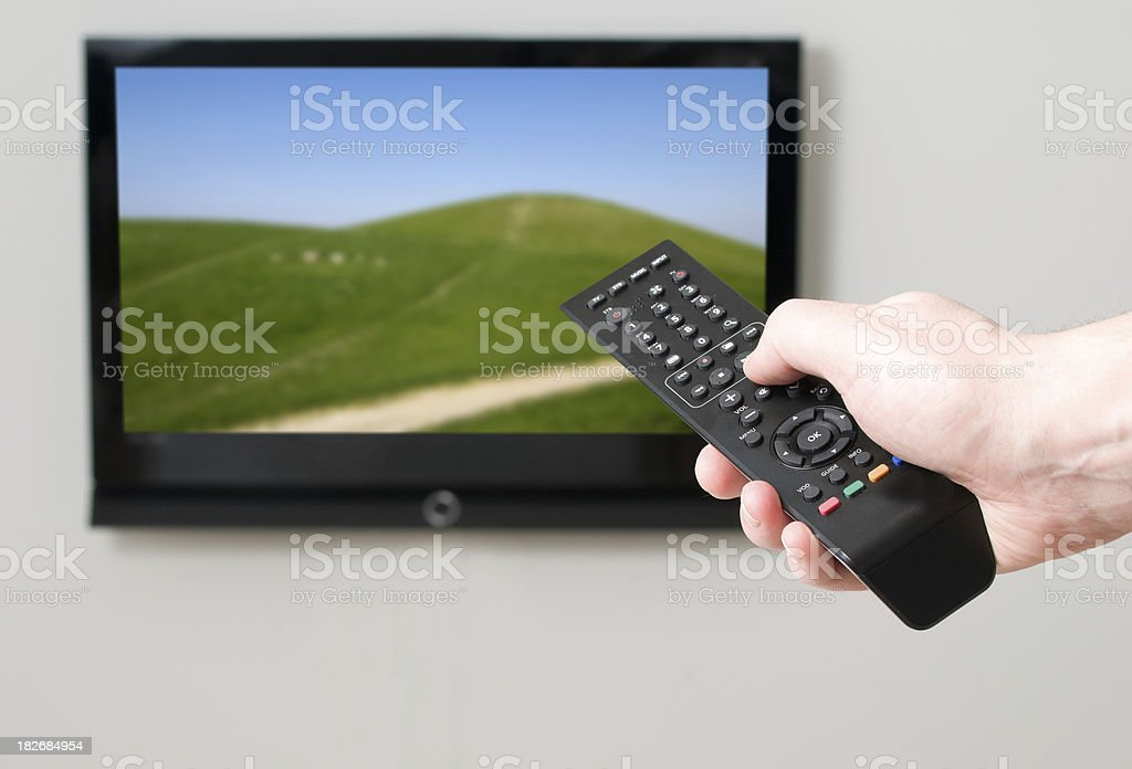 Remote control pointing a flatscreen tv with image of hills royalty-free stock photo