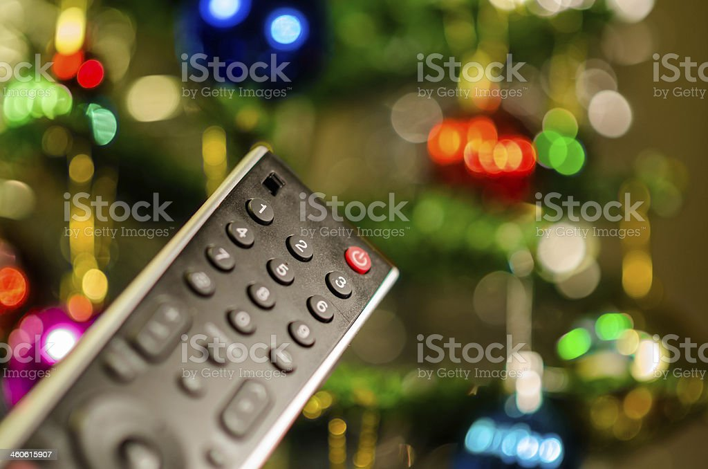 Remote control pointing toward colorful light bokeh stock photo