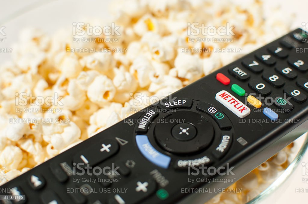 Remote control smart TV with Netflix button with popcorn. stock photo