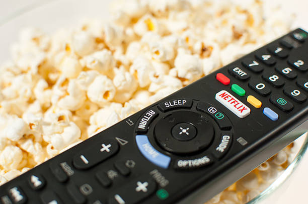Remote control smart TV with Netflix button with popcorn. Zagreb, Croatia - March 5, 2016: Remote control smart TV with Netflix button with popcorn in the background. netflix stock pictures, royalty-free photos & images