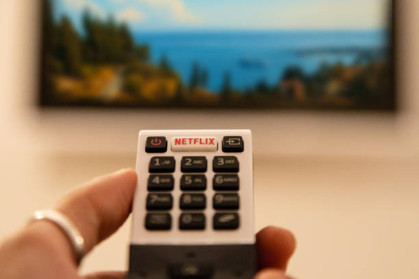 TV Remote Control with Netflix Button Ortigia, Italy - August 23, 2018: A hand holding television remote control with dedicated Netflix button in front of defocused smart tv netflix stock pictures, royalty-free photos & images