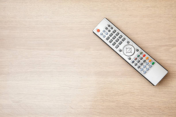 Remote controller on wooden desktop stock photo