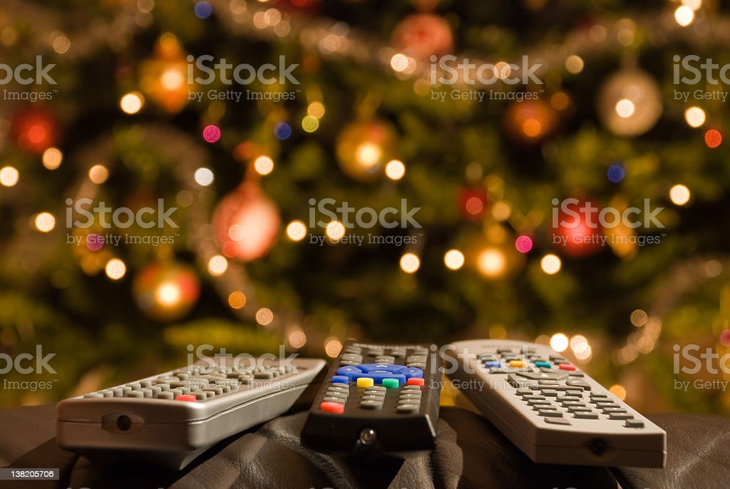 Christmas Light Remote Controls.Remote Controls In Front Of Lit Christmas Tree Stock Photo