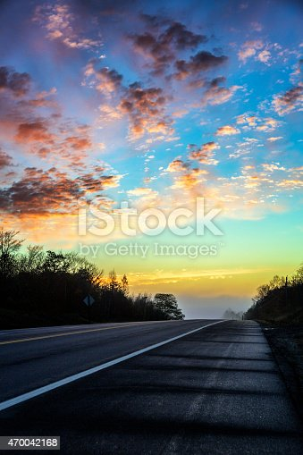 A bright, multi-colored, very early morning sunrise beyond and above the crest of a hill on a remote, wet with water dew, empty rural highway in late autumn in New England, USA. Boosted color saturation and grain. Canon 5D Mark III.