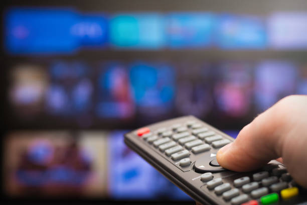 TV remote in hand stock photo