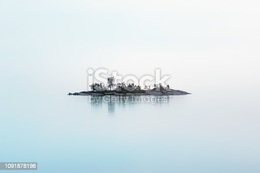 Remote rocky island with coniferous trees as if hanging in the misty air over the milky surface of the lake in a summer night. Atmospheric cool northern background with copy space. White Nights season, Lake Onega, Karelia, Russia.