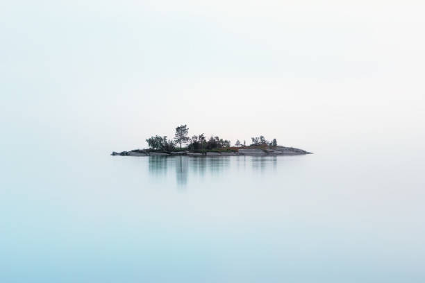 Remote Island Hanging In The Fog Over The Northern Lake Remote rocky island with coniferous trees as if hanging in the misty air over the milky surface of the lake in a summer night. Atmospheric cool northern background with copy space. White Nights season, Lake Onega, Karelia, Russia. republic of karelia russia stock pictures, royalty-free photos & images