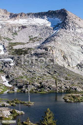 A beautiful, remote lake is surrounded by granite in the Desolation Wilderness of the Sierra Nevada Mountains in Northern California. This is a popular area for backpacking and camping.